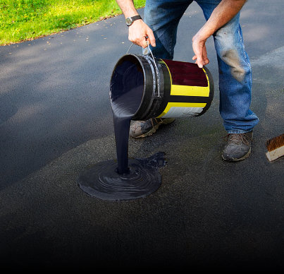 a construction worker adding asphalt cement on the road
