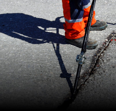 a construction worker sealing the crack on the road